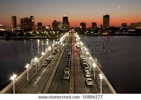 Beautiful sunset behind St. Petersburg, Florida skyline showing the city Pier in foreground - stock photo