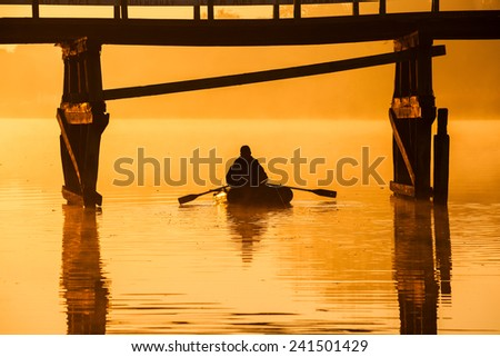 Beautiful sunset by the river. Fisherman is in the boat - stock photo