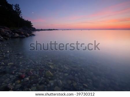 Beautiful sunset from a Swedish bay. Wide angle photo. - stock photo