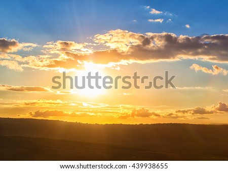 beautiful sunset in cloudy sky over field - stock photo