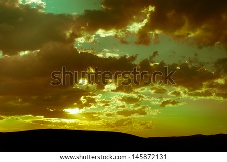 Beautiful sunset in countryside with cloudy sky. Vintage style processing image - stock photo