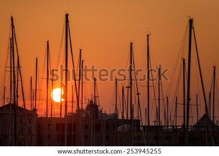 Beautiful sunset in the marina - Red sun sets behind boats masts - stock photo
