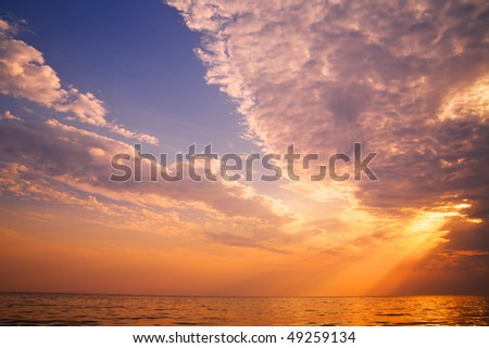 Beautiful sunset in the tropical sea. Sun through clouds - stock photo