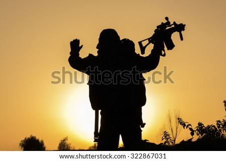 Beautiful sunset of soldier crouched in uniform holding his riffle high up