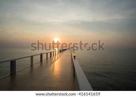Beautiful sunset on beach and bridge in silhouette twilight golden hour/Sunset on beach and bridge silhouette - stock photo