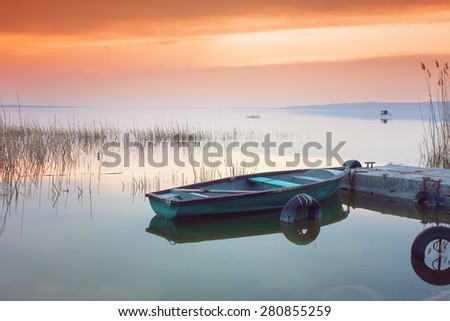 Beautiful sunset on Lake Balaton with anchored boat - stock photo