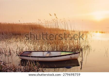 Beautiful sunset on lake Balaton with deserted rowboat - stock photo