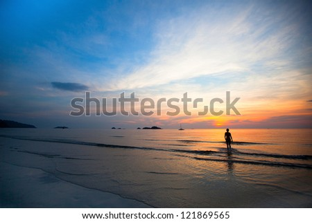 Beautiful sunset on sea beach, swimming girls silhouette in background.