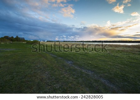 Beautiful sunset on spring field. Latvia. - stock photo