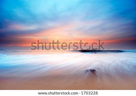 beautiful sunset on the beach (slow shutterspeed) - stock photo