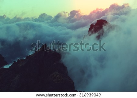 Beautiful sunset on the hill above clouds - stock photo
