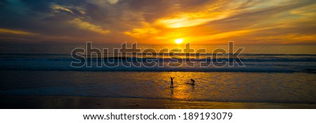 Beautiful Sunset on the ocean with silhouettes of surfers - stock photo