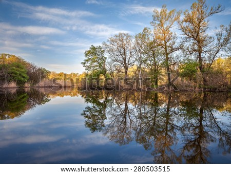 Beautiful sunset on the river in forest with sky reflection. Spring in Ukraine