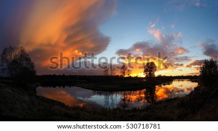 Beautiful sunset on the river. Landscape and silhouette of trees