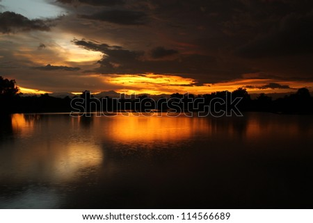 Beautiful sunset on the water and falling rain in nakhonsawan province, Thailand. - stock photo