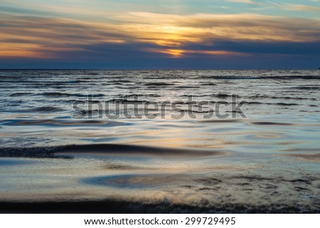 Beautiful sunset over Baltic sea, waves and sun