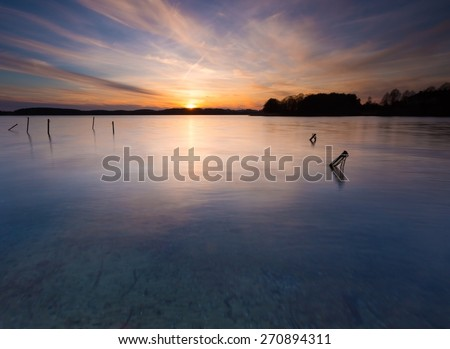 Beautiful sunset over calm lake in Mazury lake district. After sunset sky reflecting in water, calm vibrant landscape. Krzywe lake near Olsztyn, Poland. - stock photo