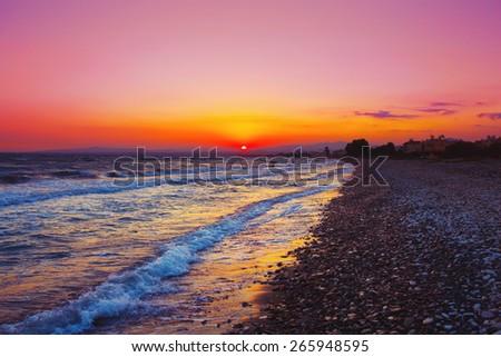 Beautiful sunset over Mediterranean sea. Pebble stone beach. - stock photo