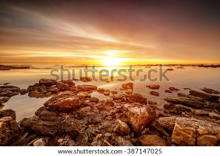 Beautiful sunset over sea, amazing peaceful beach landscape, picturesque view from stony seaside, beauty of nature - stock photo