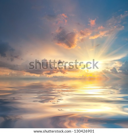 Beautiful sunset over sea with reflection in water, majestic clouds in the sky - stock photo
