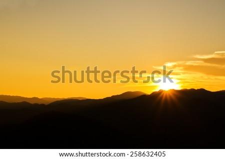 Beautiful sunset over silhouette mountain - stock photo