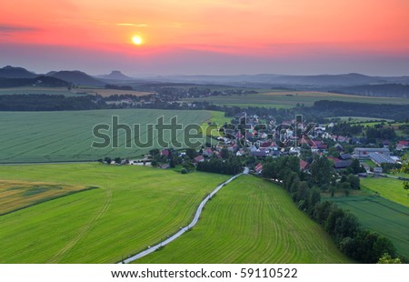 beautiful sunset over small city in saxony mountain - stock photo