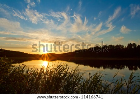 Beautiful sunset over the forest lake - stock photo