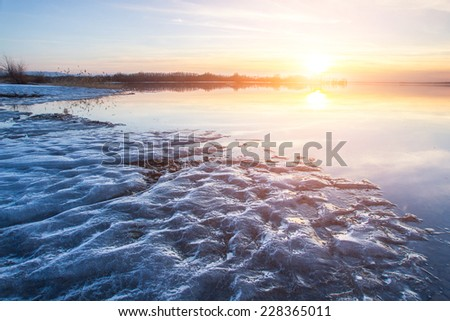 Beautiful sunset over the frozen lake winter