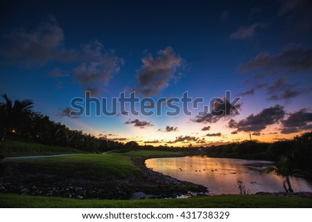 Beautiful sunset over the lake near the golf course in a tropical resort in Punta Cana, Dominican Republic - stock photo