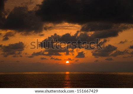 Beautiful sunset over the sea. Curly fluffy clouds