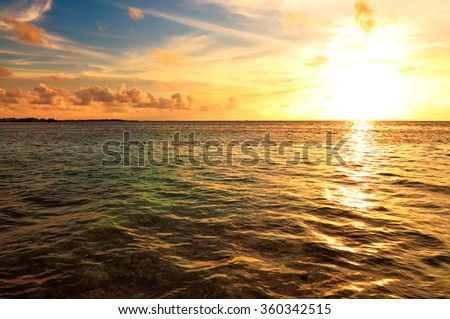 Beautiful sunset over the sea on a cloudy day in Maldives. - stock photo