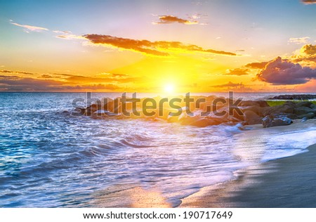 Beautiful sunset over the sea with a view at stony shore on the white beach on a Caribbean island of Barbados - stock photo
