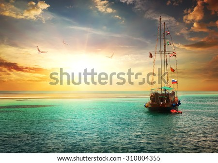 Beautiful sunset over yacht in the sea - stock photo