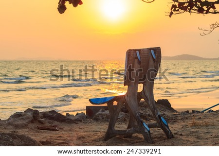 Beautiful sunset scene at sea and blue bench - stock photo