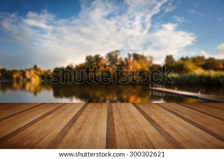 Beautiful sunset sky reflected in Autumn Fall lake with wooden planks floor - stock photo