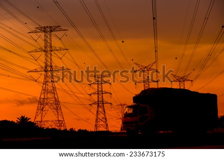 Beautiful sunset view of high-voltage tower and transportation - stock photo