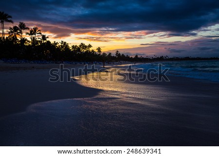Beautiful sunset view of surf at beach with golden glow of sun reflecting off of water. - stock photo