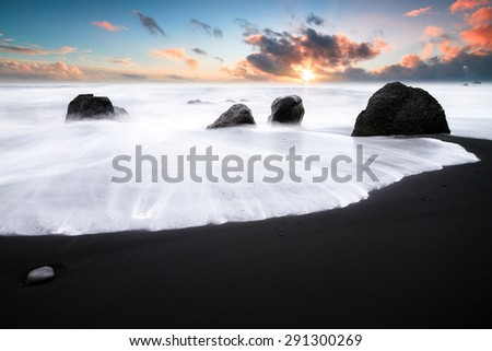 Beautiful sunset view of the black sand and rough sea at the beach of Vik in Iceland - stock photo