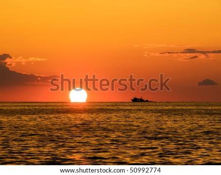 Beautiful sunset with a fishing boat on the horizon somewhere along the Adriatic coast.