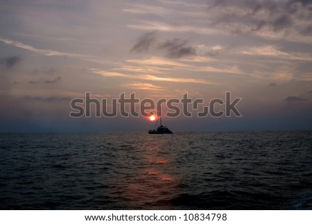 Beautiful sunset with boat crossing suns path on the waters.  Pink, blue and orange. - stock photo
