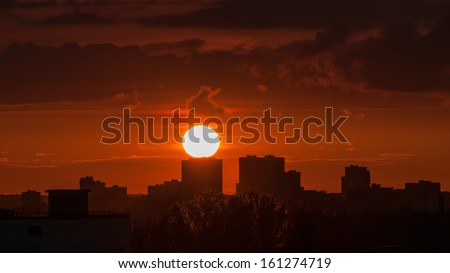 Beautiful sunset with bright Sun over skyline. Moscow, Russia.