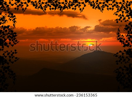 Beautiful sunset with cloud and mountain,tree foreground siluette frame,orange color tone - stock photo