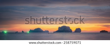 beautiful sunset with colorful dramatic sky and mountains over the ocean, Thailand - stock photo