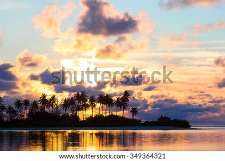 Beautiful sunset with dark silhouettes of palm trees and amazing cloudy sky in tropical island - stock photo