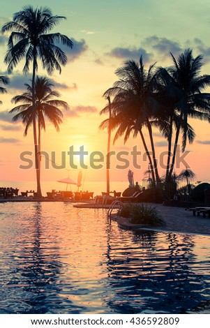 Beautiful sunset with palm trees silhouettes on a tropical beach. - stock photo