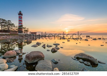 Beautiful sunset with rocks in still water and lighthouse on background - stock photo