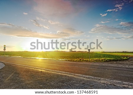 Beautiful sunset with rural road in colours - stock photo
