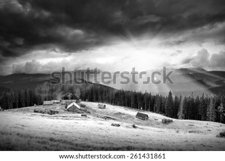 Beautiful sunset with shining sun under low dark clouds in a Carpathian mountain valley with rustic wooden village on a forest hill. Monochrome colors - stock photo