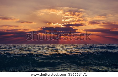 Beautiful sunset with sunbeams over the sea in red and yellow colors. Sunset seascape - stock photo