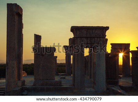 Beautiful Sunset with warm orange glow behind ruins of Tachara Palace or Palace of Darius from Achaemenid Empire in Persepolis of Shiraz. - stock photo